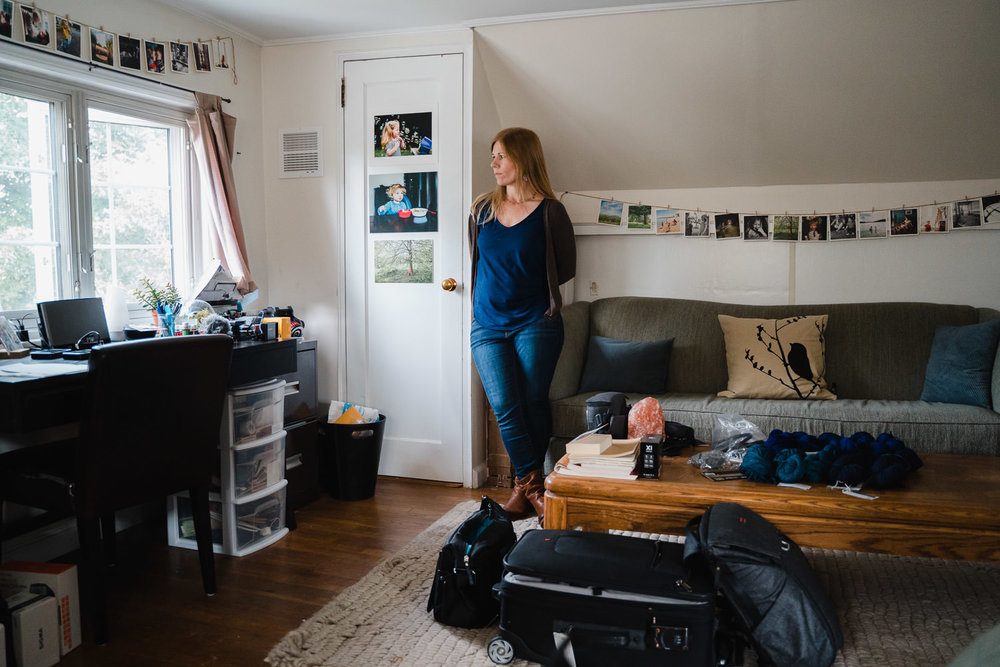A woman stands in her home office.