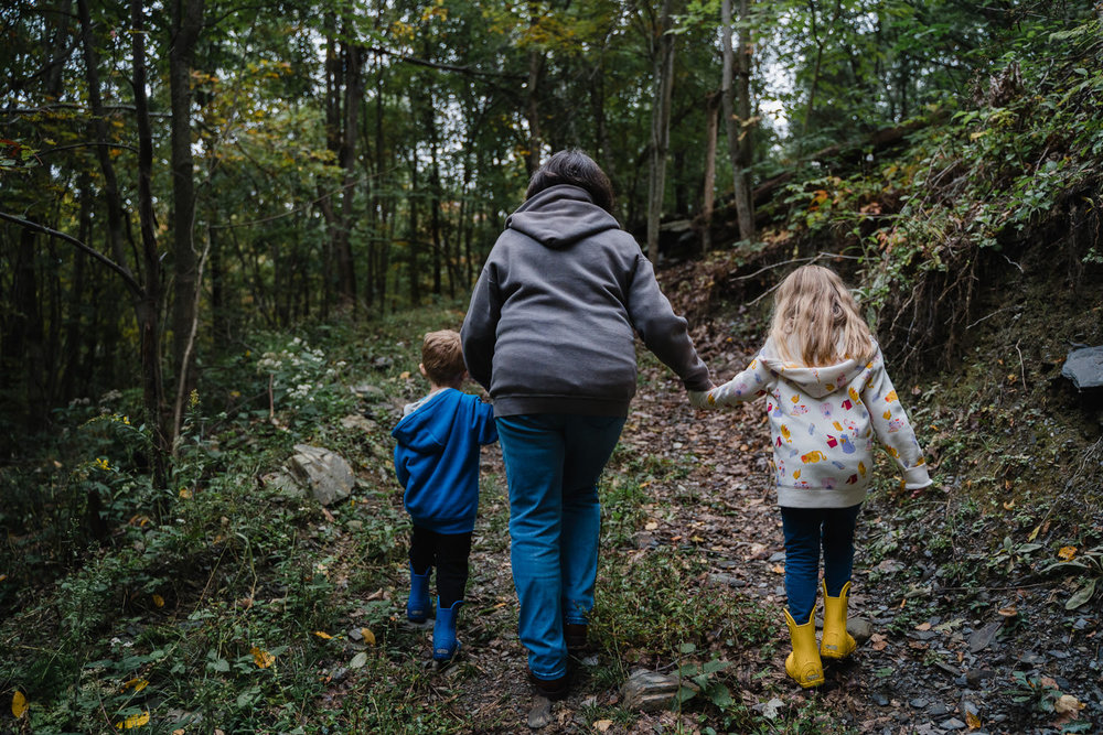 A woman walks up a trail holding the hands of two children.
