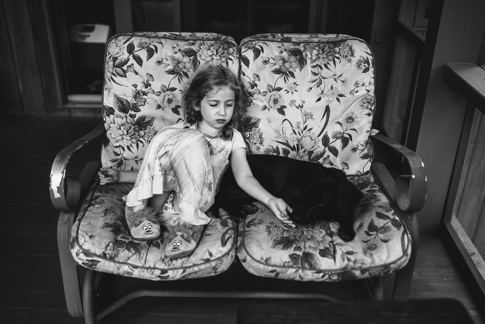 A little girl sits on a chair with her dog.