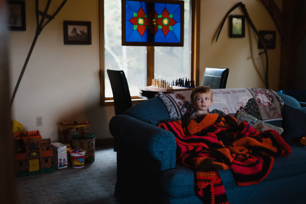 A little boy sits on a couch adnd watches TV.