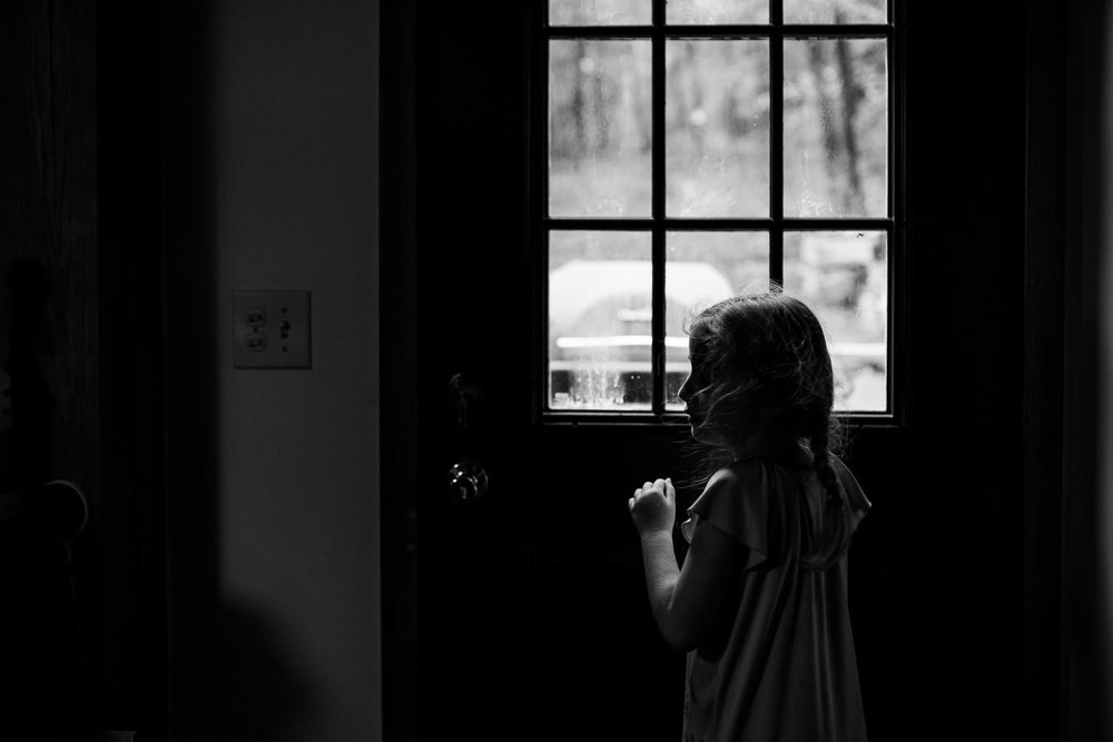 A little girl looks out a window.