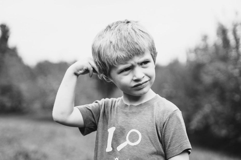 A little boy scratches his head.