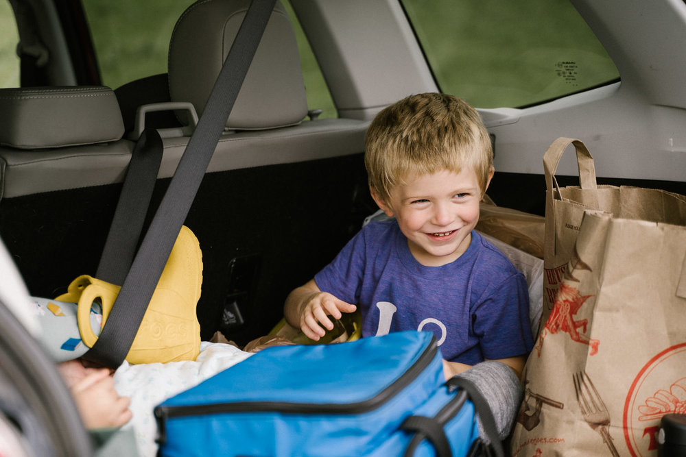 Two children sit in the back of a car.