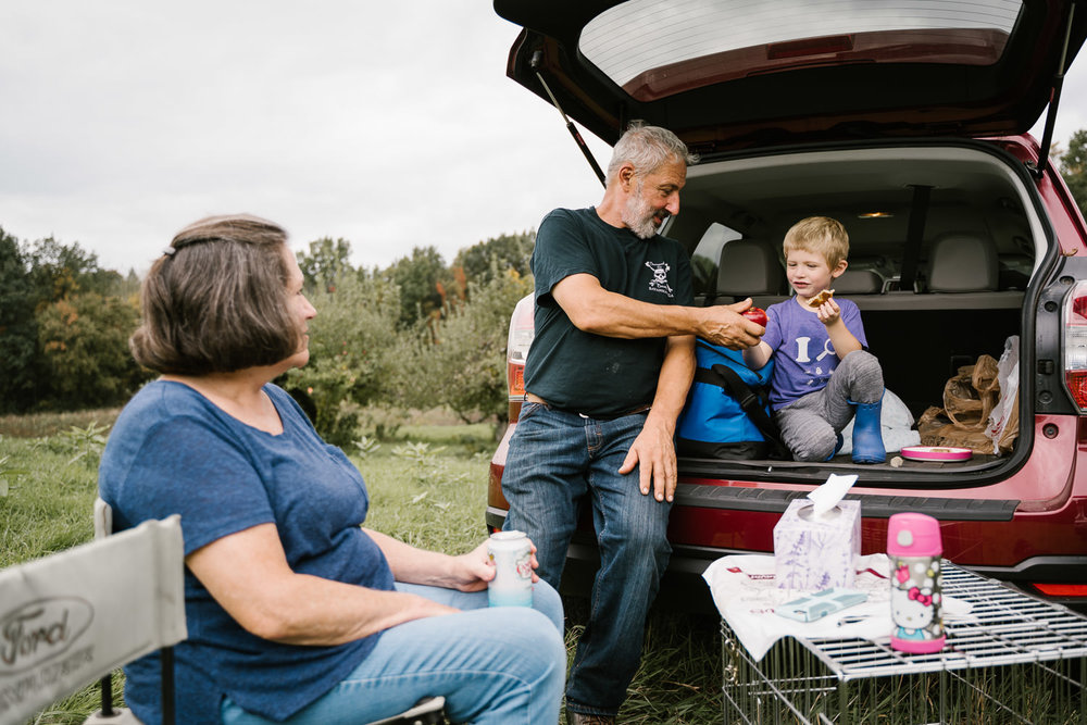A family picnics out of the back of their car.