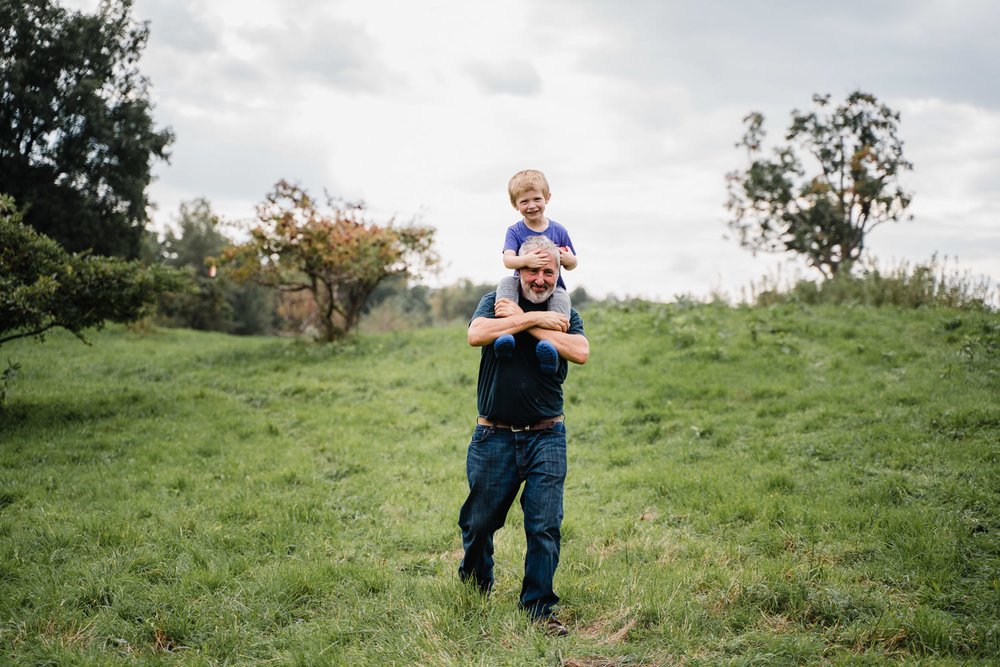 A man carries his grandson on his shoulders.