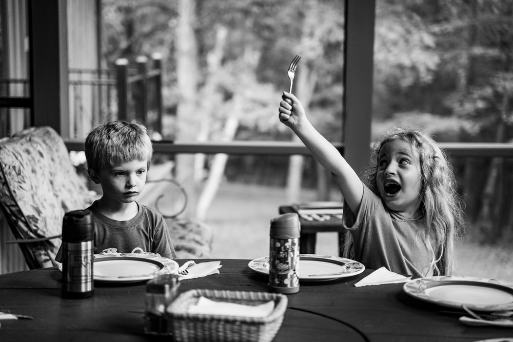 A little girl holds up her fork at the table.