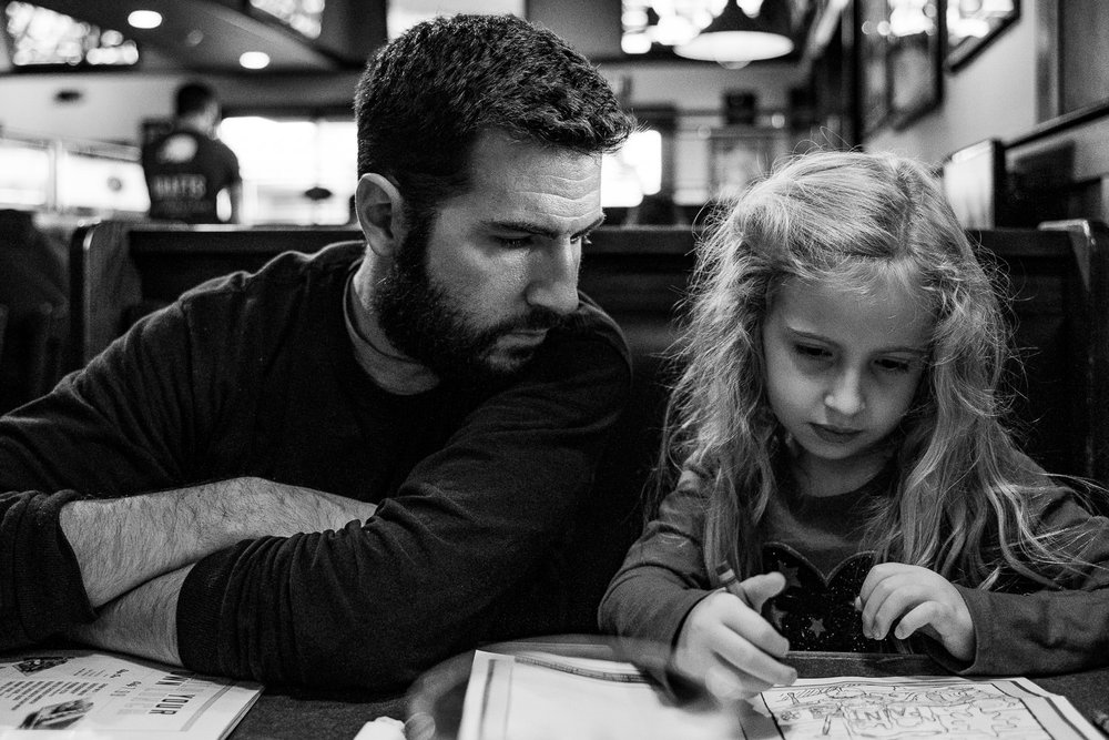 A girl and her father sit together at a restaurant.