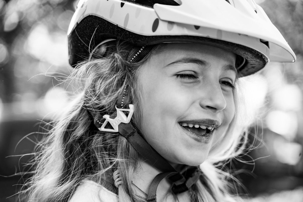 A little girl in a bike helmet laughs.