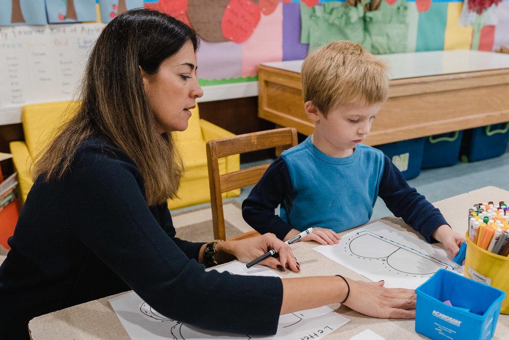 """A teacher helps a preschooler write a """"B""""."""