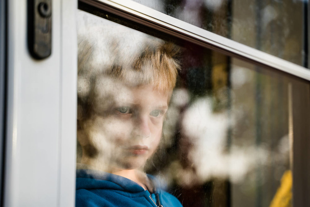 A little boy looks out his glass storm door.
