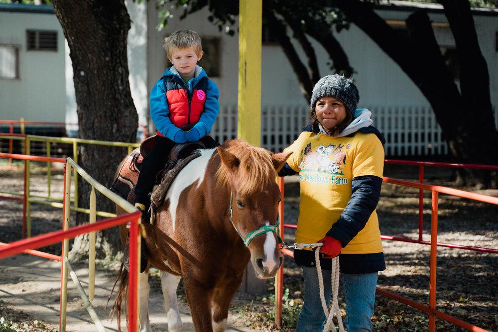 A little boy rides a pony at Green Meadows Farm.