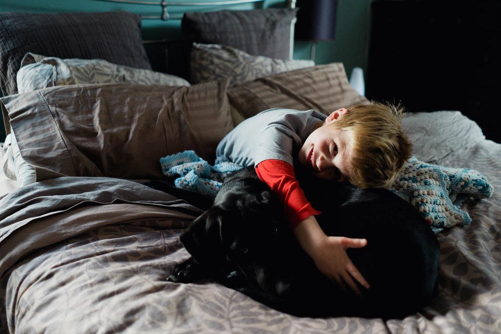 A little boy hugs his black lab puppy.