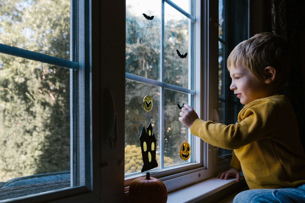 A little boy hangs Halloween gel clings on his living room windo