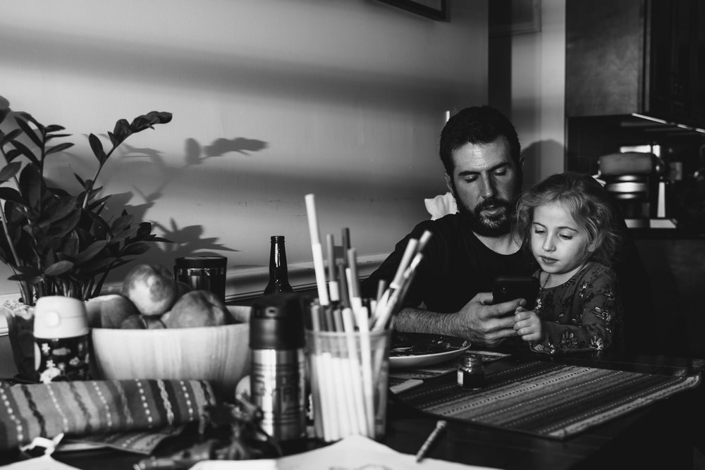 A man and his daughter sit at the kitchen table.