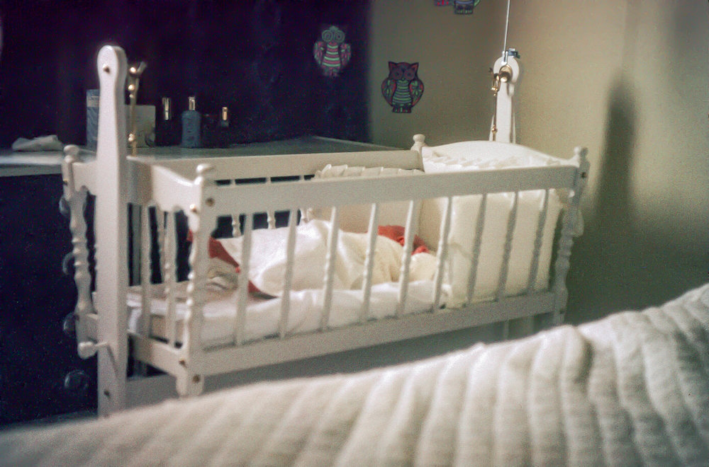 Me as a newborn in a crib next to my parents' bed.