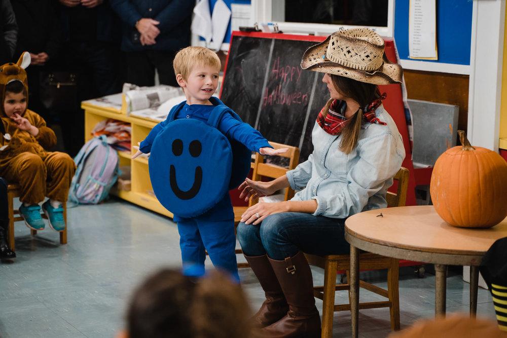 A little boy shows his teacher his Halloween costume.