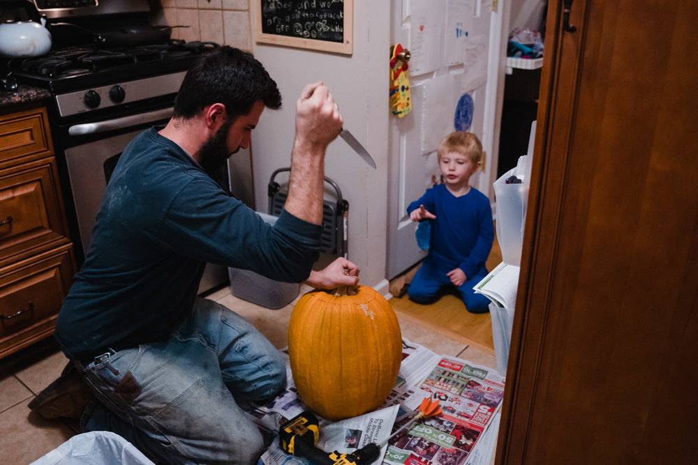 A father and son carve a pumpkin.