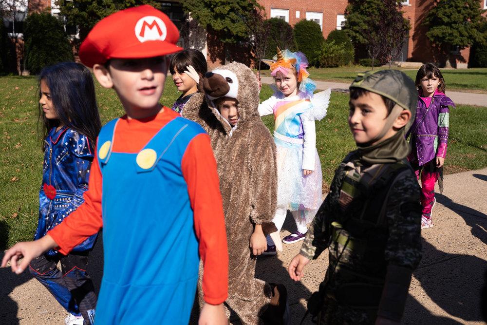 School children march in a Halloween parade.
