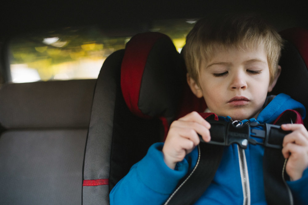 A little boy buckles his car seat.