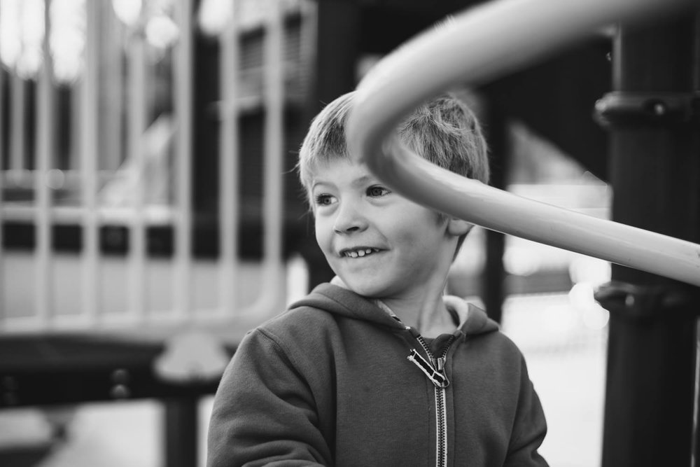 A little boy smiles on the playground.