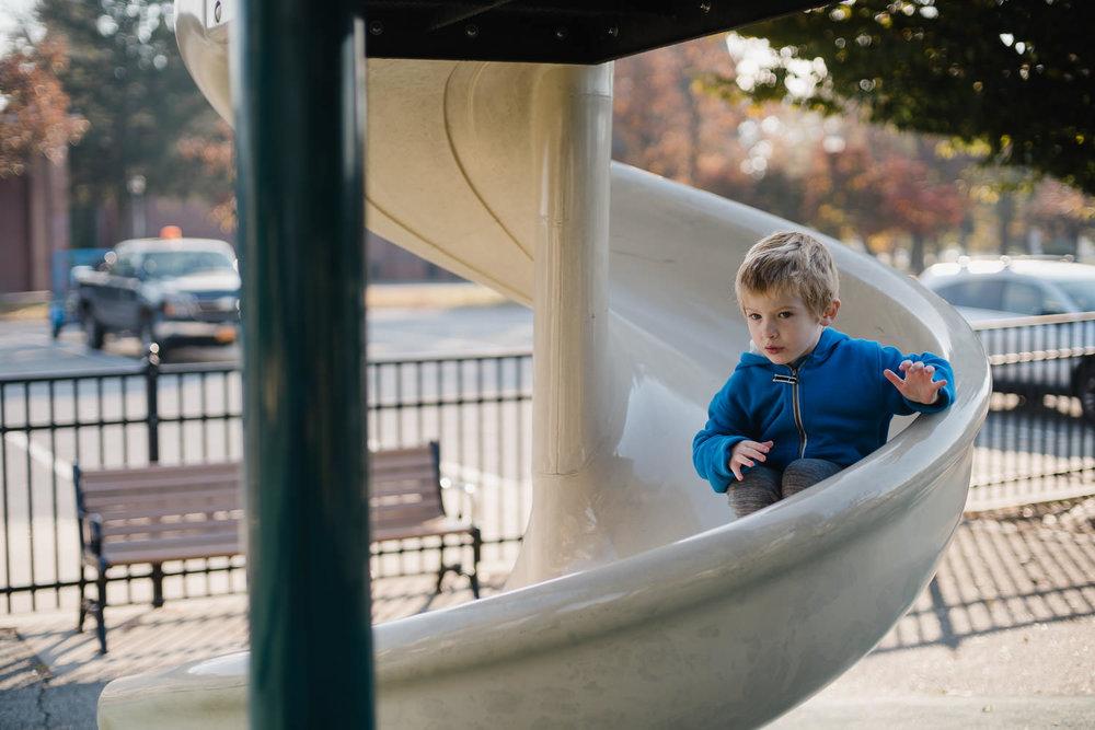 A little boy goes down a slide.
