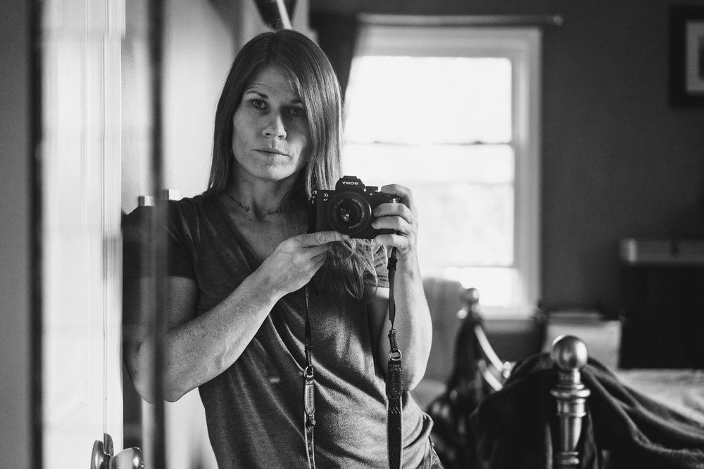A woman takes a self-portrait in a mirror.