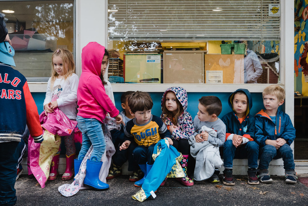 PReschoolers sit on a wall outside their classroom.