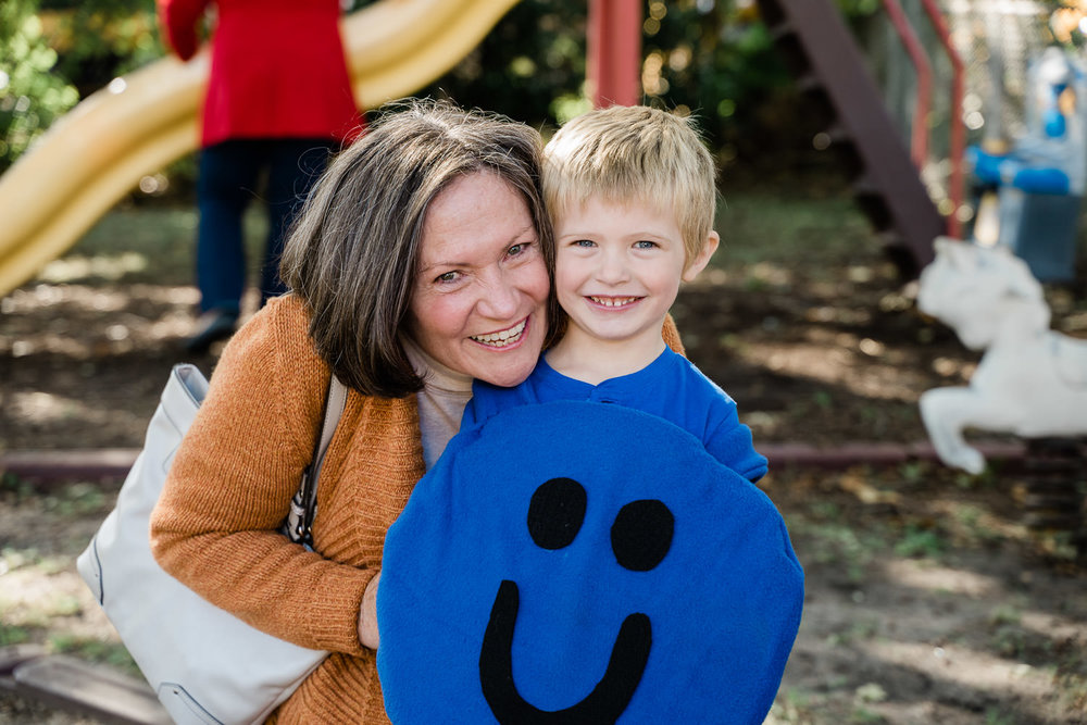A little boy in his Halloween costume poses with his grandmother