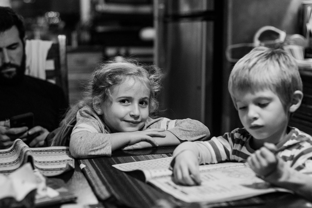 A little girl sits at the kitchen table with her brother.