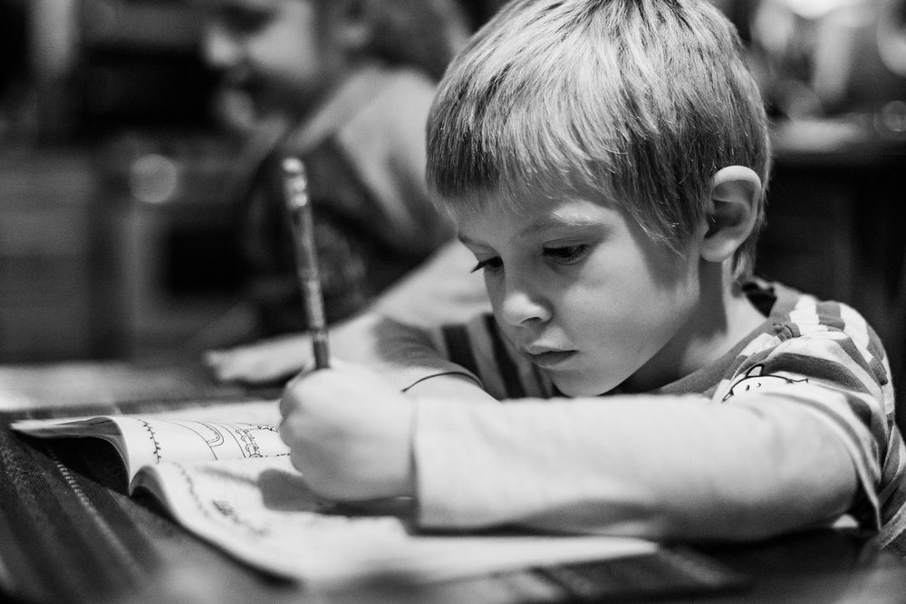 A little boy works in a workbook.