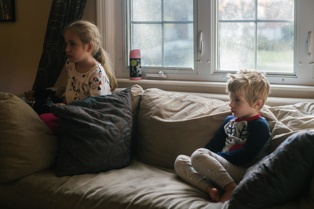 Two kids sit on a couch and watch TV.
