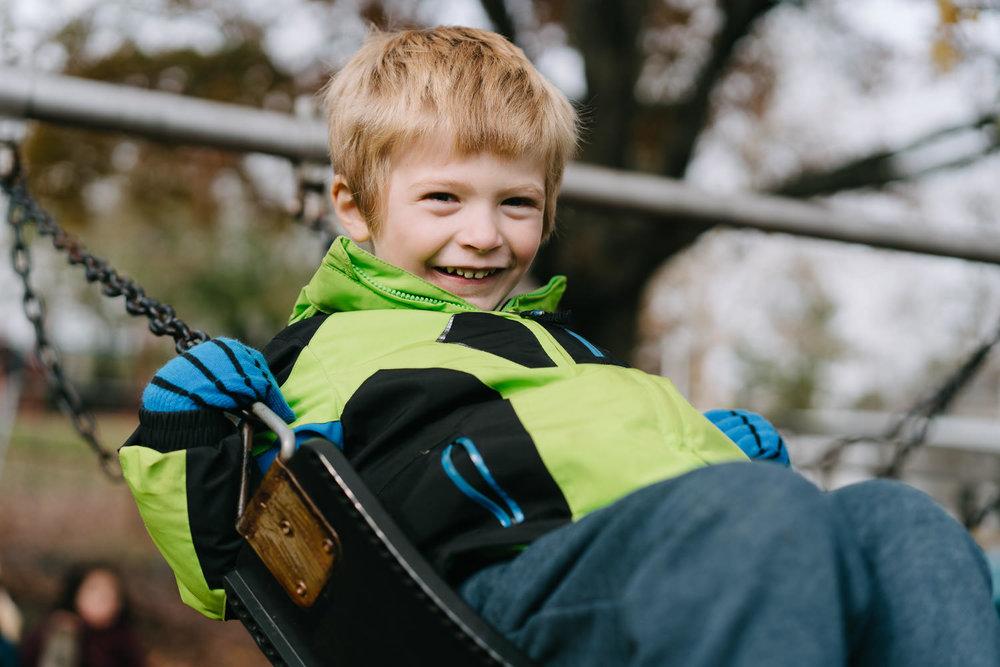 A boy swings on a swing.