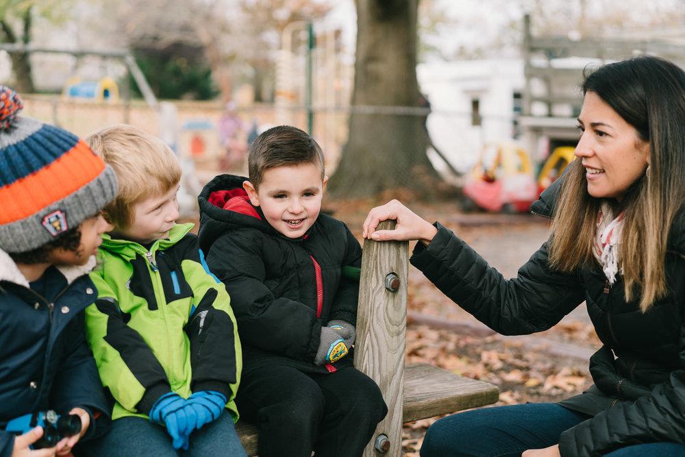 A teacher talks to three children.
