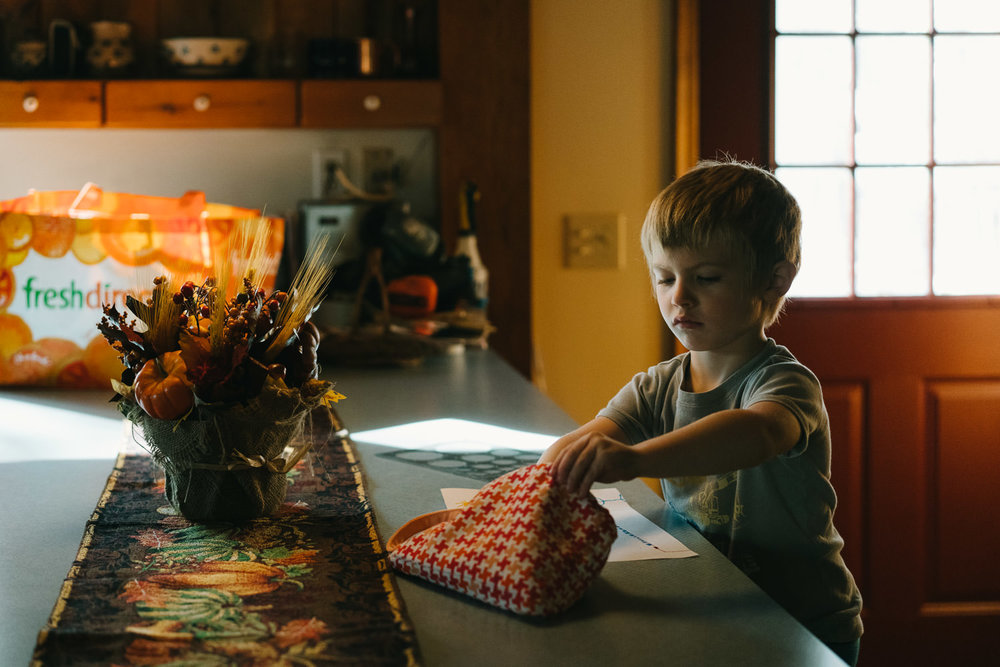 A little boy draws at the kitchen counter.