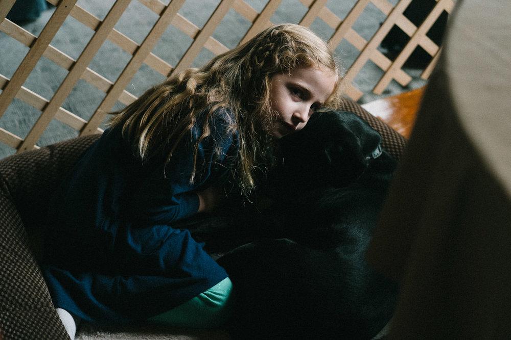 A little girl hugs her dog.