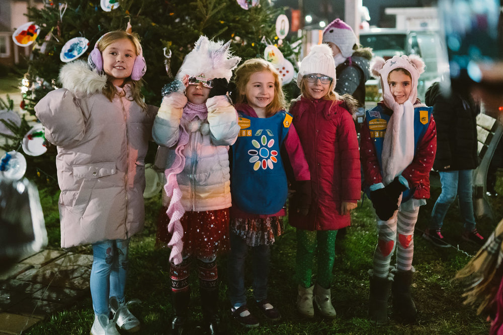 Girls gather in front of a town Christmas tree.