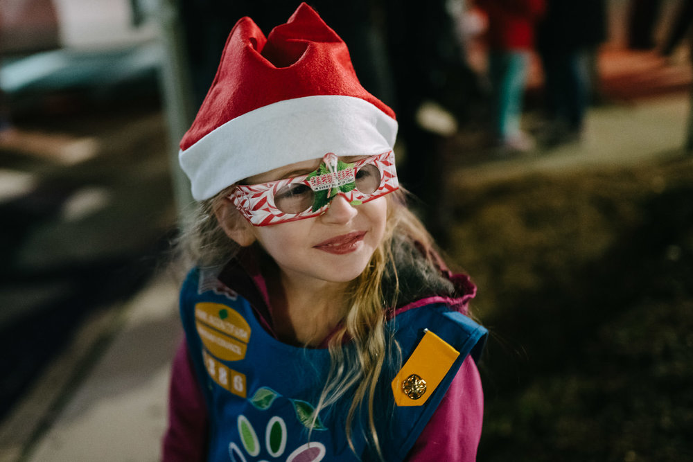 A little girl scout in a Santa hat and 3D glasses.
