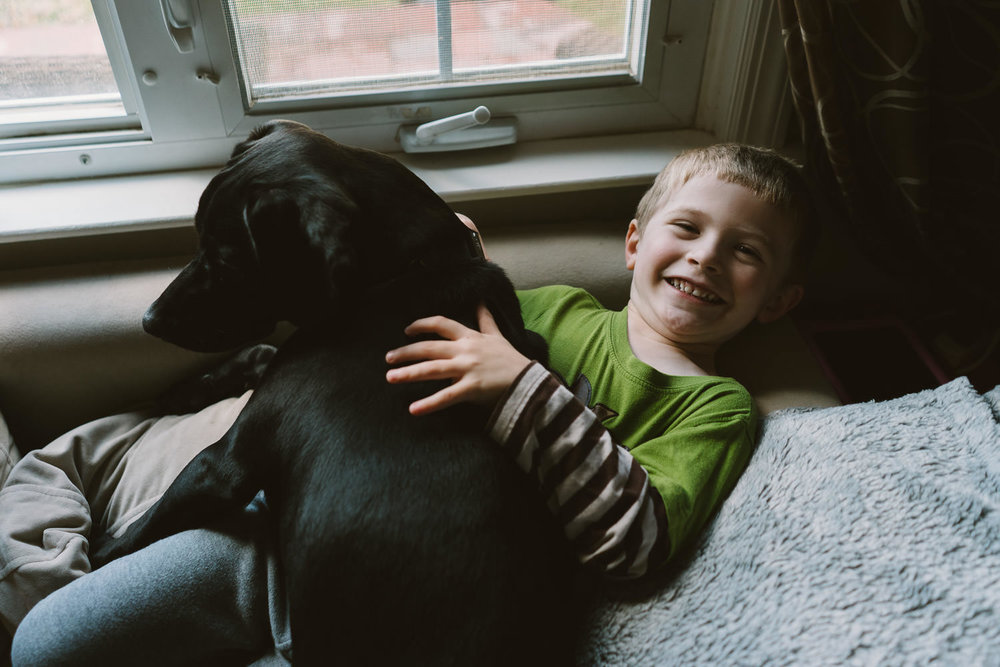 A little boy hugs his dog.