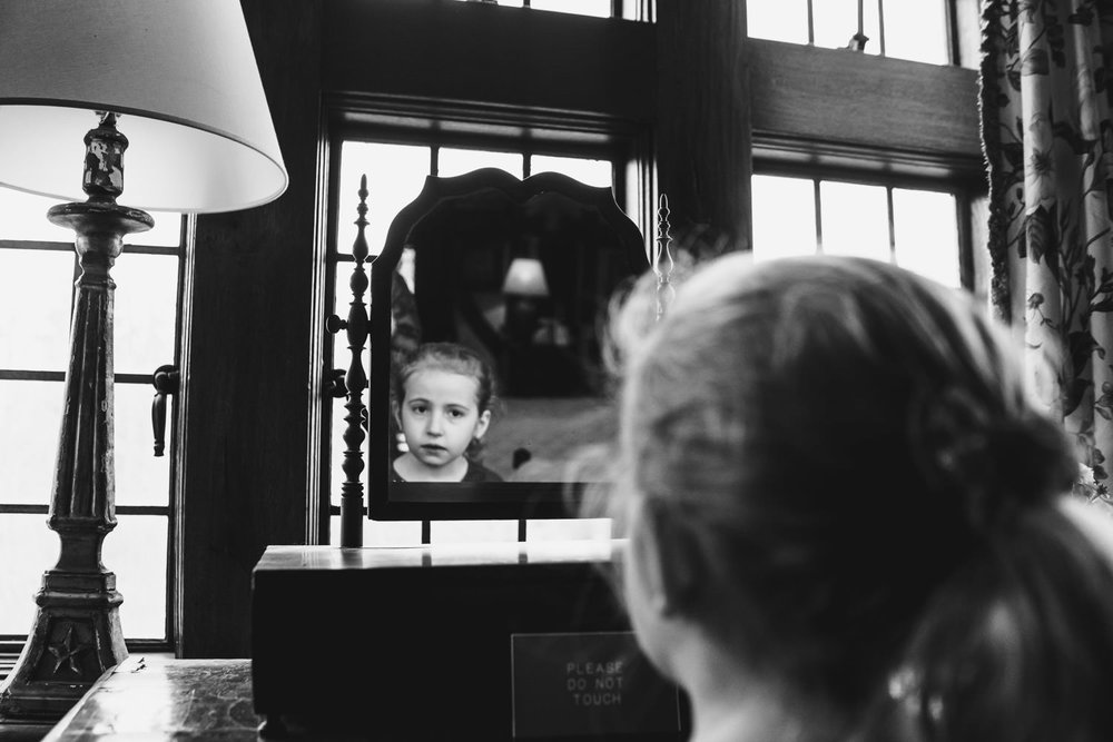 A little girl looks in a mirror at the Coe House.