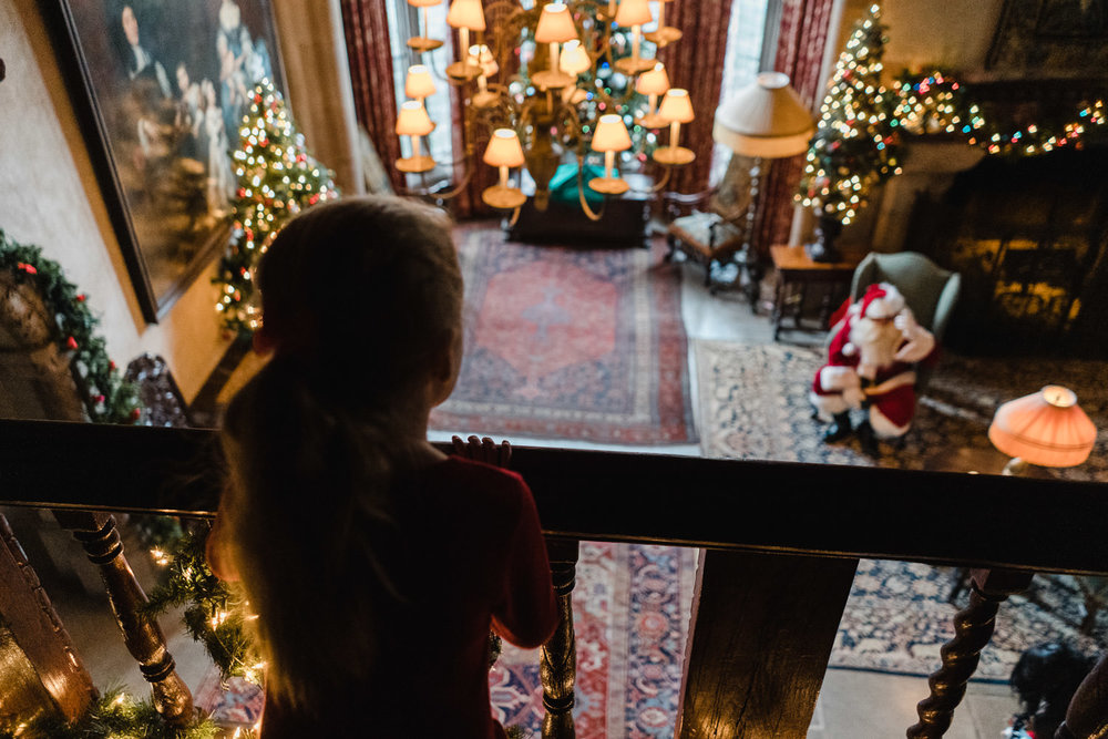 A little girl looks over a balcony at Santa Claus at Coe House.