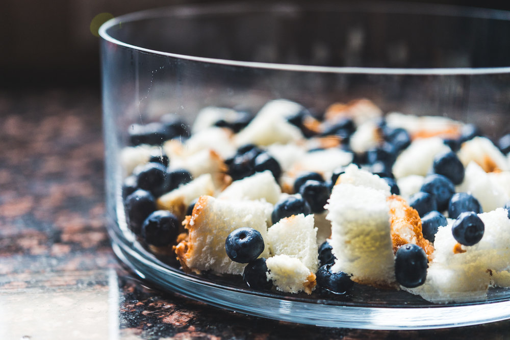 Making a trifle of blueberries and angel food cake.