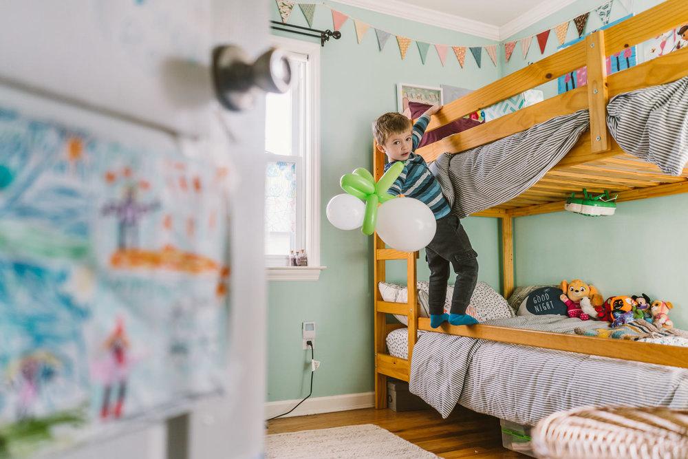 A little boy throws a balloon off a bunkbed.