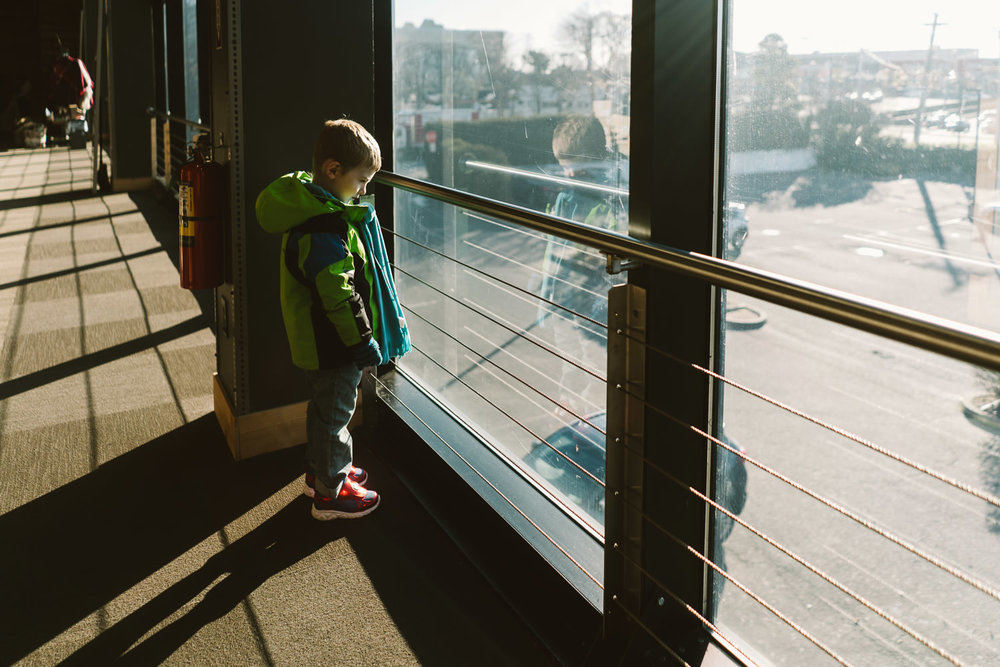 A little boy looks out a window onto a parking lot.