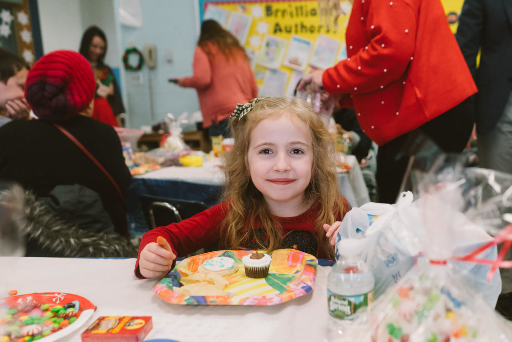 A little girl sits at her desk during a classroom holiday party.