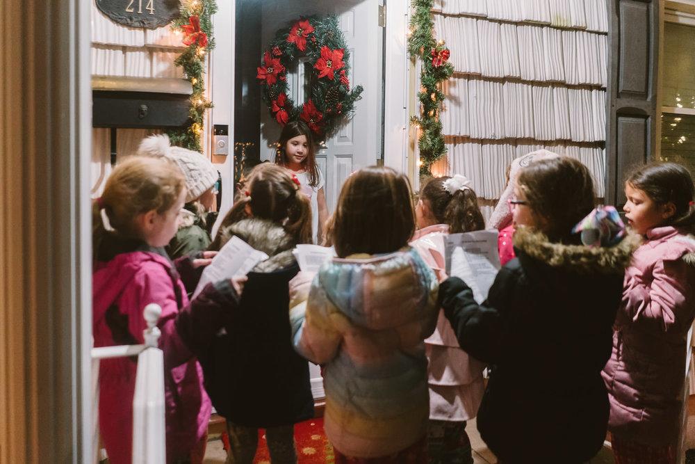 Little girls carol at a front door.