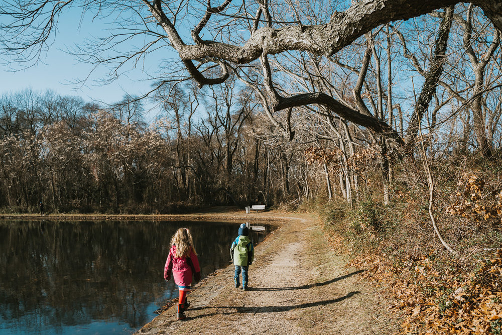 Two children walk along Hempstead Lake.