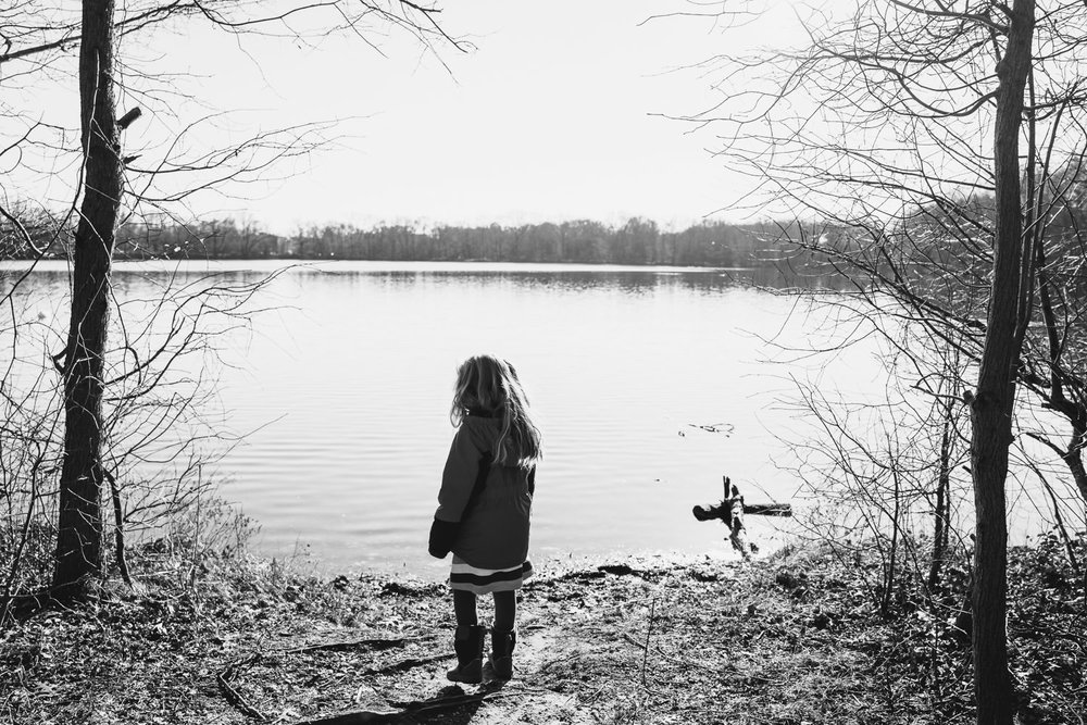 A little girl looks out at Hempstead Lake.