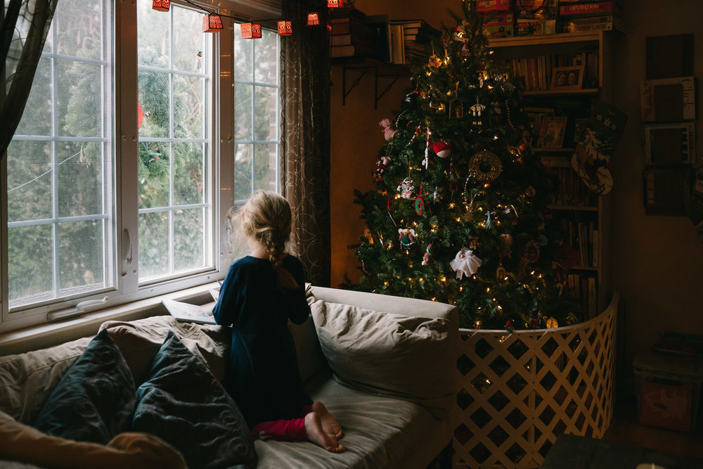 A little girl sits on a couch next to a Christmas tree.