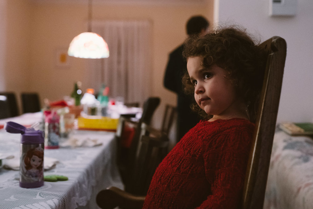A little girl sits at the dinner table on Christmas.