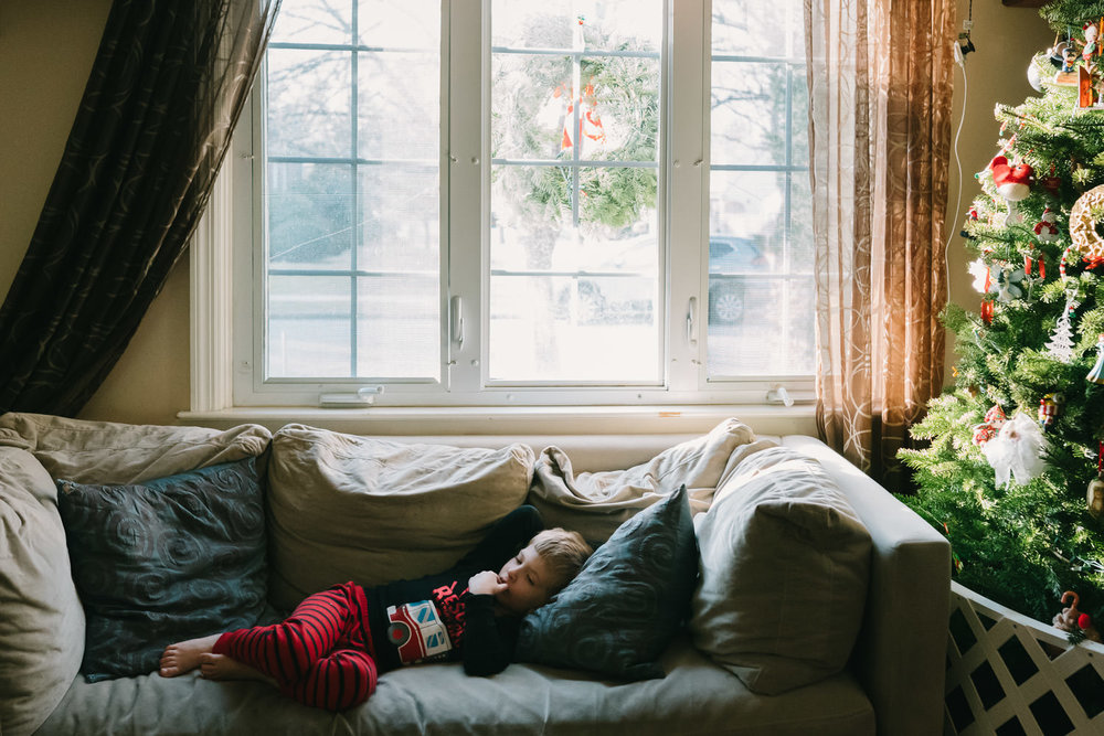 A little boy relaxes on a sofa at Christmas time.